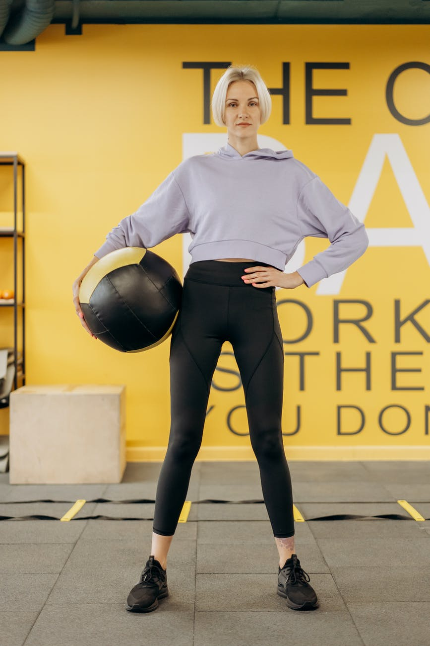 woman standing with an exercise ball